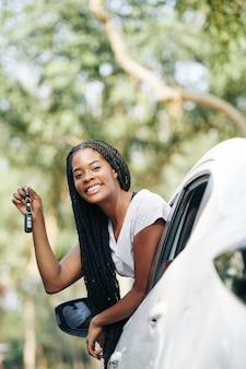 Mujer feliz mostrando las llaves del coche