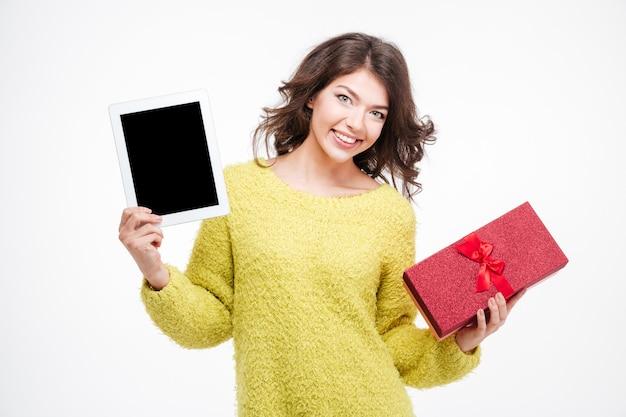 Mujer feliz mostrando la pantalla de la tableta en blanco y sosteniendo una caja de regalo aislada sobre un fondo blanco.