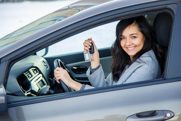 Mujer feliz muestra las llaves del coche nuevo.