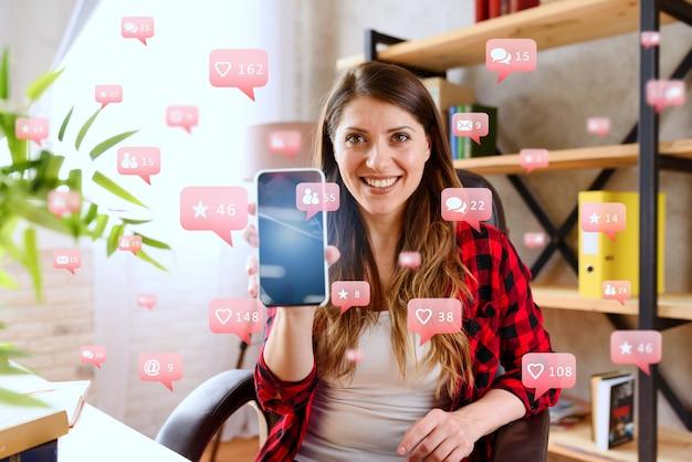 Mujer feliz muestra su teléfono inteligente con mensajes de redes sociales, chat e iconos de usuarios