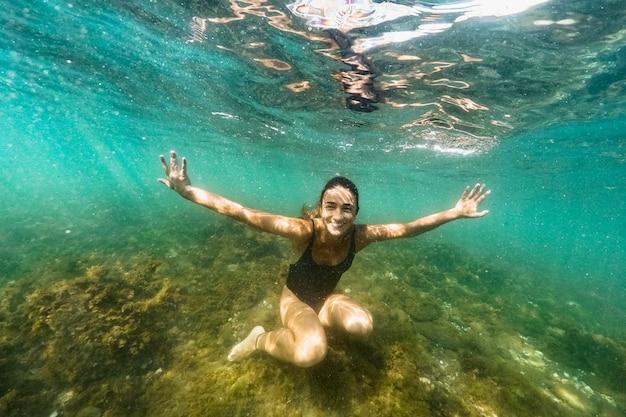 Mujer feliz nadando bajo el agua