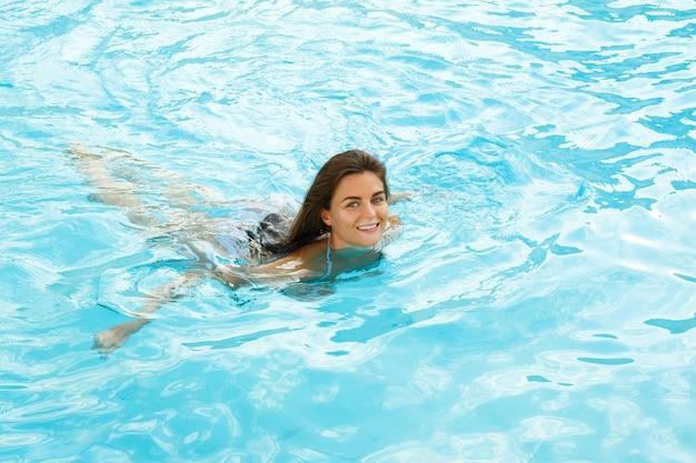 Mujer feliz nadar en la piscina
