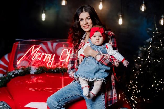 Mujer feliz con una niña con un lazo rojo en la cabeza está sentada y divirtiéndose en coche retro en estudio de navidad.