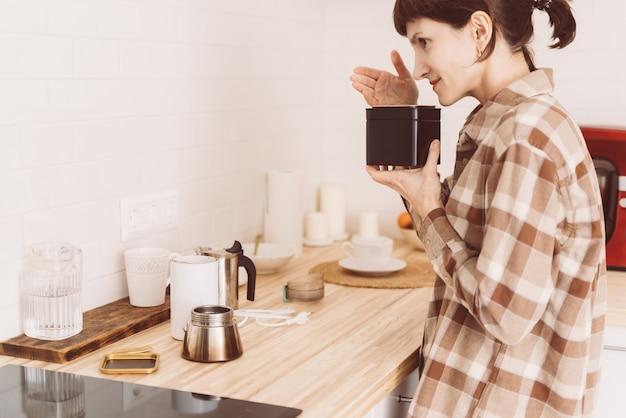 Mujer feliz oliendo café de lata y oliendo aroma. mujer inhalando frijoles frescos