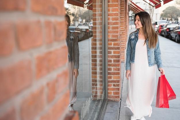 Mujer feliz con paquetes de compras caminando en la calle cerca de las ventanas de la tienda