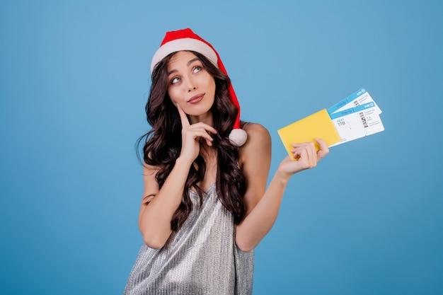 Mujer feliz con pasajes de avión y pasaporte con sombrero de navidad aislado sobre azul