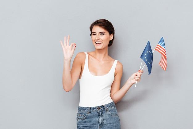 Mujer feliz patriótica sosteniendo banderas europeas y estadounidenses y mostrando gesto bien sobre fondo gris