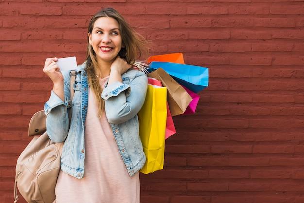 Mujer feliz de pie con bolsas de compra y tarjeta de crédito en la pared de ladrillo rojo