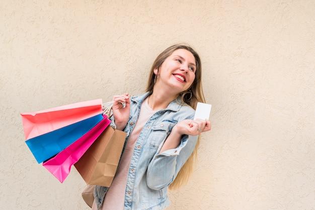 Mujer feliz de pie con bolsas de compra y tarjeta de crédito en la pared