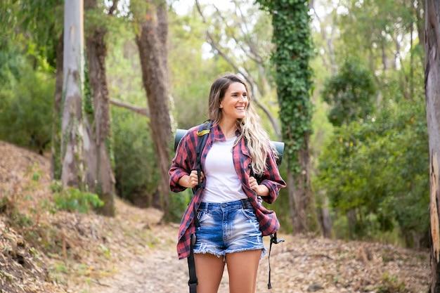 Mujer feliz de pie en el camino forestal, sonriendo y mirando a otro lado. mujer de pelo largo con mochilas y senderismo en la naturaleza. concepto de turismo, aventura y vacaciones de verano.