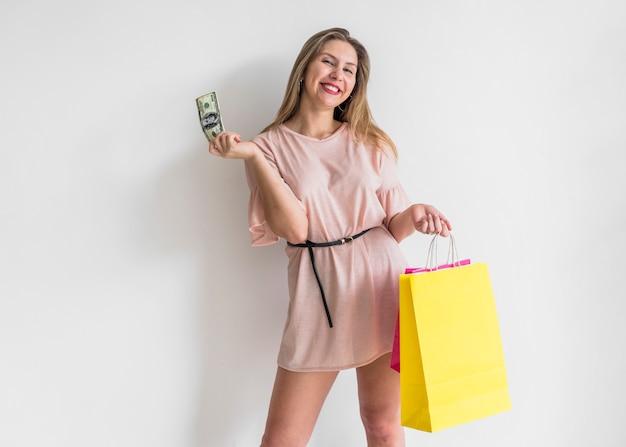 Mujer feliz de pie con dinero y bolsas de compras