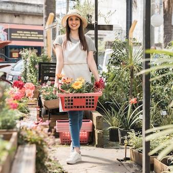 Mujer feliz de pie en invernadero con contenedor de flores frescas