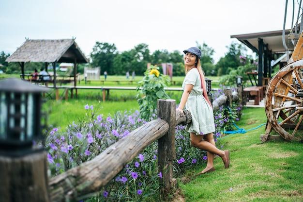 Mujer feliz de pie en el jardín de flores en las barandillas de madera