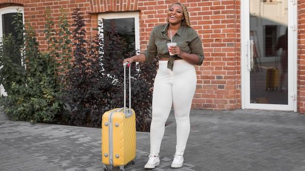 Mujer feliz de pie junto a su equipaje amarillo