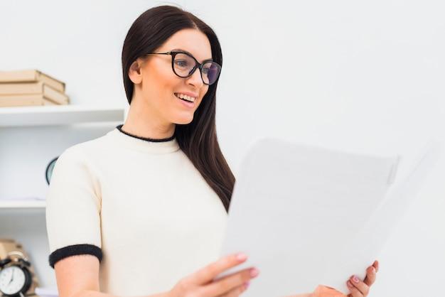 Mujer feliz de pie con papeles en la oficina