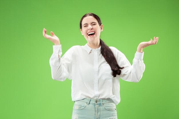 Mujer feliz de pie y sonriendo aislado sobre fondo verde de estudio. hermoso retrato femenino de medio cuerpo.