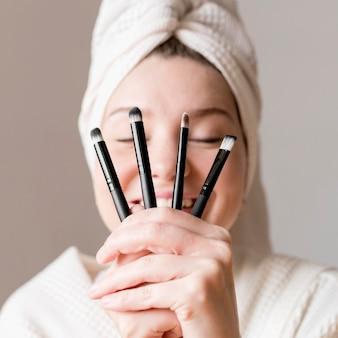 Mujer feliz con pinceles de maquillaje