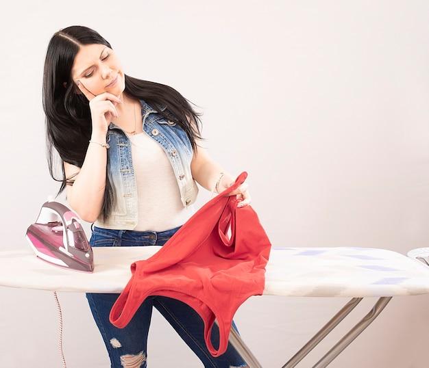 Mujer feliz planchando ropa con plancha eléctrica aislado