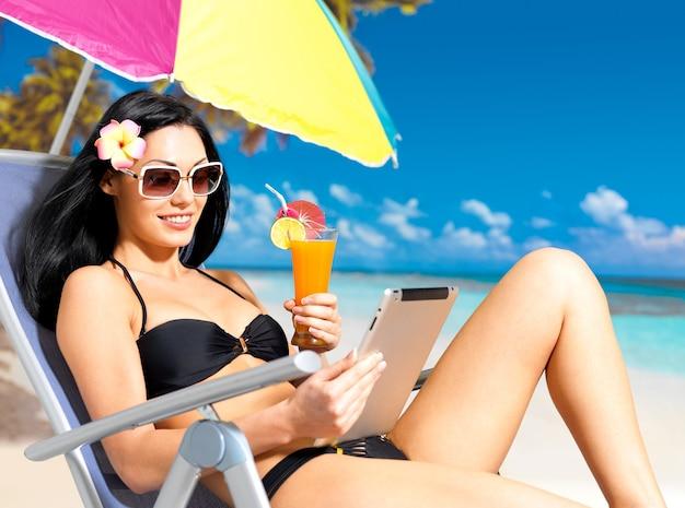 Mujer feliz en la playa con ipad.