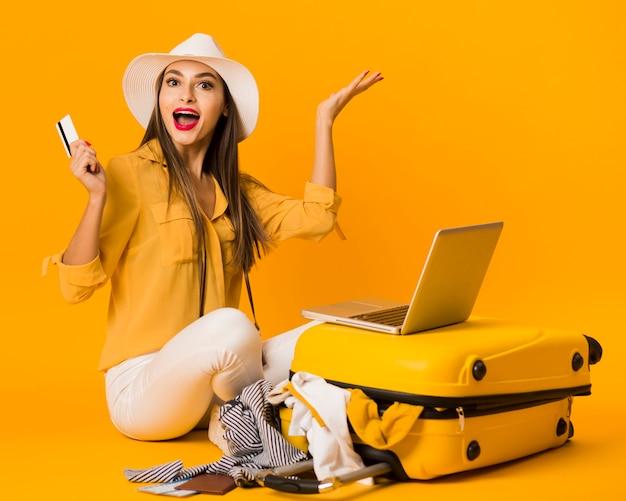 Mujer feliz posando junto al equipaje mientras sostiene la tarjeta de crédito
