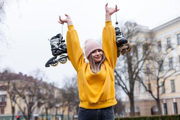Mujer feliz posando mientras sostiene patines