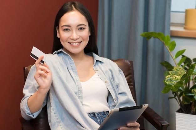 Mujer feliz posando mientras sostiene la tarjeta de crédito y tableta
