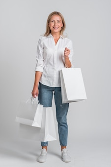 Mujer feliz posando con un montón de bolsas de la compra.