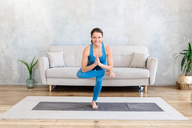 Mujer feliz practicando deportes en casa haciendo estiramientos de yoga