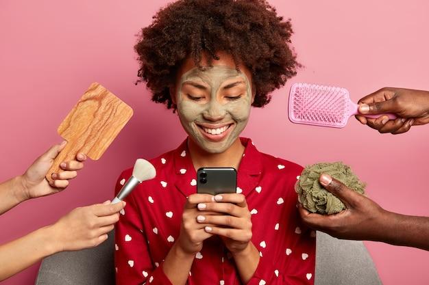 Mujer feliz se prepara para la cita, mensajes con el novio, hace procedimientos de belleza para tener un aspecto perfecto, usa pijama