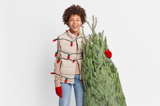 Mujer feliz se prepara para las vacaciones lleva un árbol de navidad recién cortado comprado en el mercado callejero envuelto con una guirnalda retro tiene un ambiente festivo