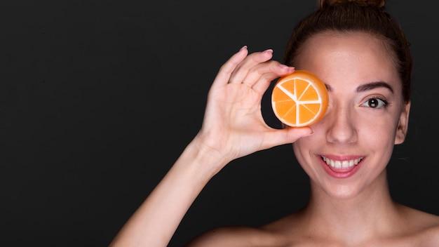 Mujer feliz con producto para el cuidado de la piel