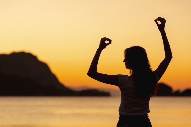 Mujer feliz y puesta de sol en el fondo
