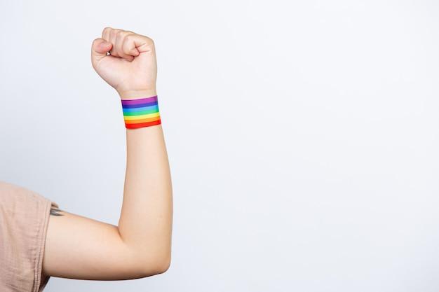 Mujer feliz con pulsera arcoiris lgbt.