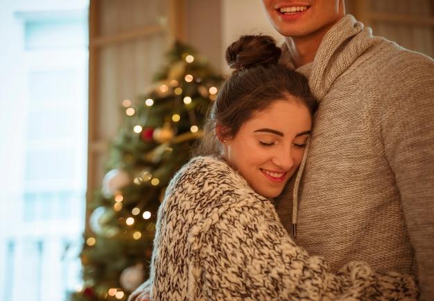 Mujer feliz que abraza al hombre en el árbol de navidad