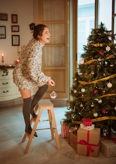 Mujer feliz que adorna el árbol de navidad con el juguete