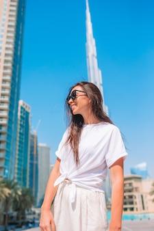 Mujer feliz que camina en dubai con el rascacielos de burj khalifa en el fondo.