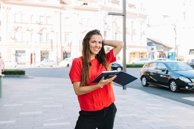 Mujer feliz que se coloca en la acera que sostiene el diario