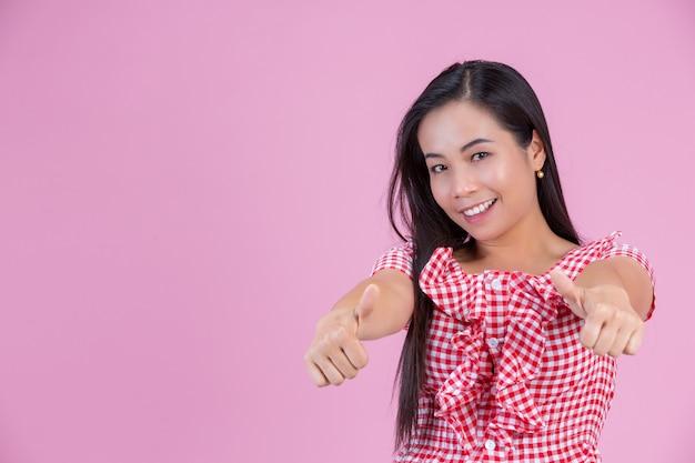 Mujer feliz que da los pulgares para arriba