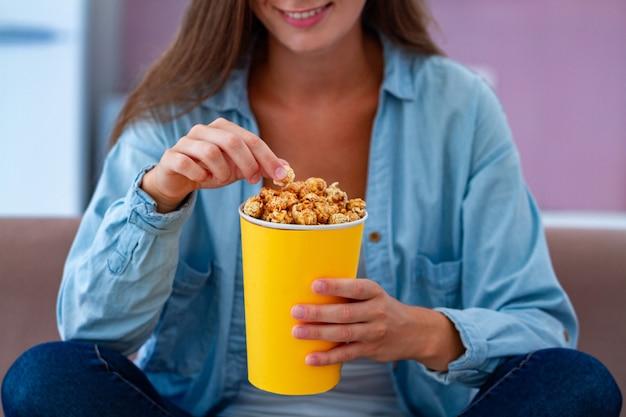 Mujer feliz que descansa y que come las palomitas crujientes del caramelo mientras que ve la tv en casa. película de palomitas de maíz