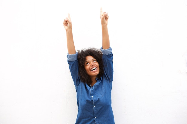 Mujer feliz que destaca y que sonríe contra el fondo blanco