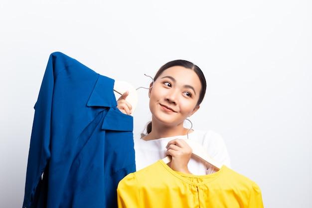 Mujer feliz que elige la blusa aislada sobre el fondo blanco