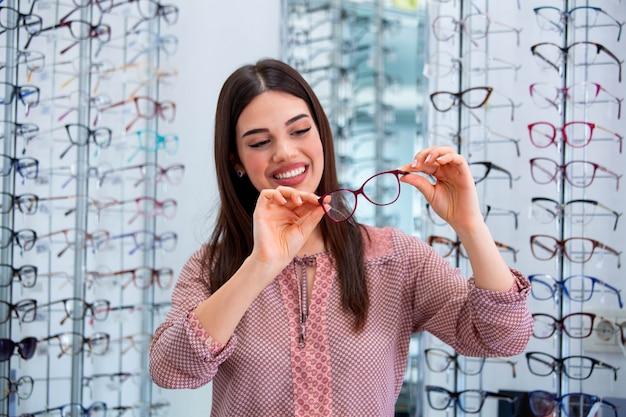 Mujer feliz que elige los vidrios en la tienda de óptica