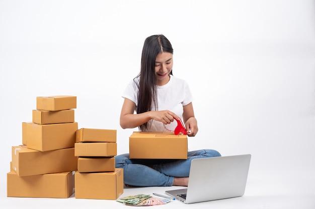 Mujer feliz que está empacando cajas en ventas en línea concepto de trabajo en línea