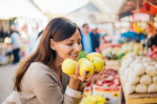 Mujer feliz que goza del olor fresco de la paprika en el mercado.