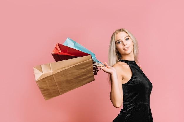 Mujer feliz que lleva bolsos de compras coloridos