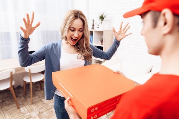 Mujer feliz que mira la caja de la pizza y el mensajero.