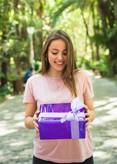 Mujer feliz que mira la caja de regalo púrpura