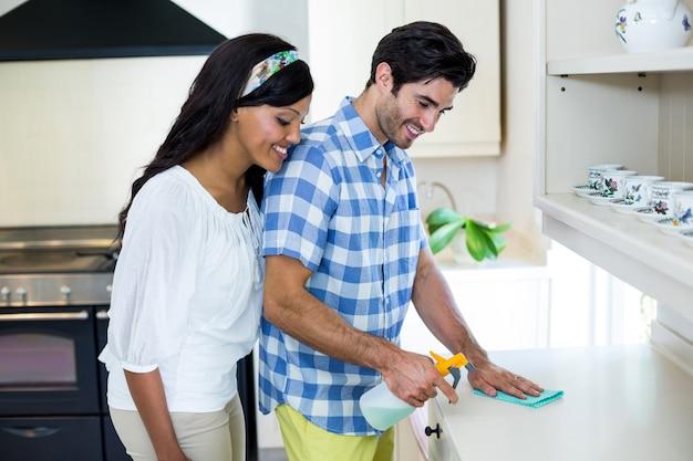 Mujer feliz que mira mientras que el hombre de limpiar la cocina