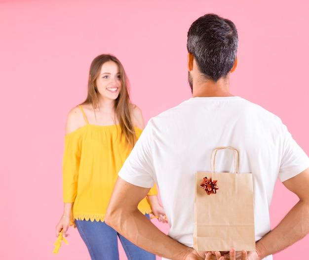 Mujer feliz que mira a su novio que sostiene las cajas de regalo contra fondo rosado