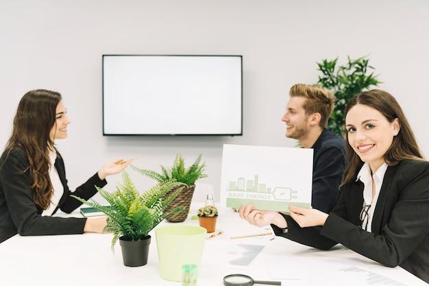Mujer feliz que muestra concepto de ahorro de energía en papel en la oficina